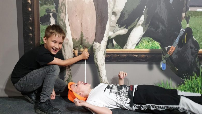 boys milking cow at 3D exhibition in Malaga